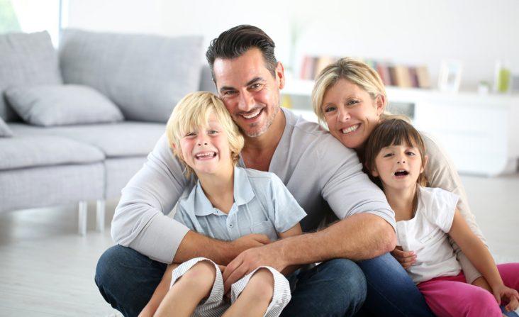 Portrait of happy family sitting on floor